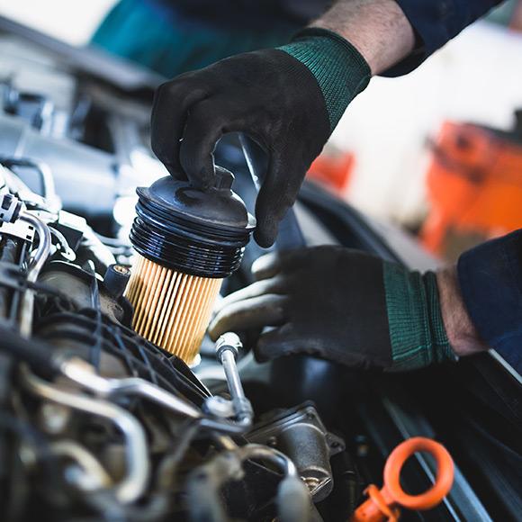 Mechanic working on car promoting motor trade insurance in Hexham