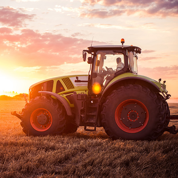 Tractor at sunset promoting farm insurance in Hexham