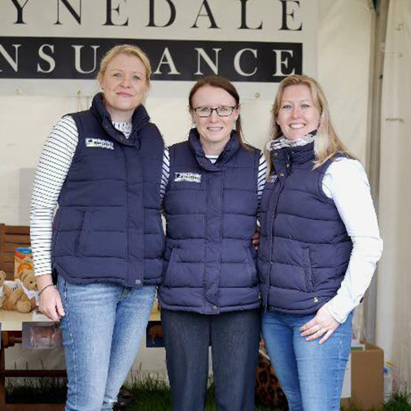Three members of staff at Tynedale Insurance Brokers smiling in front of their stall in Hexham